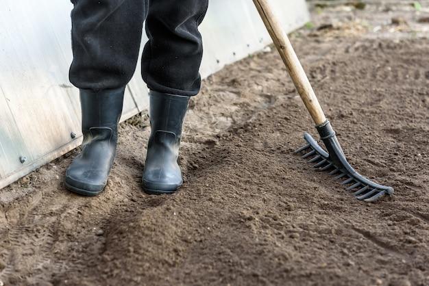 Coltivatore che lavora in giardino con terreno di livellamento del rastrello. preparazione del terreno per la semina.