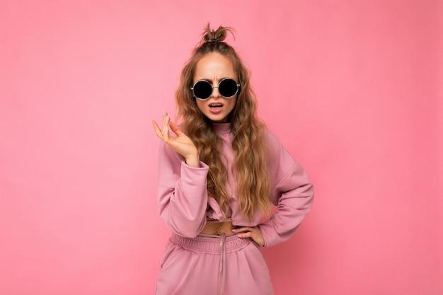 Affascinante donna riccia bionda adulta insoddisfatta isolata sopra la parete rosa del fondo che porta casuale