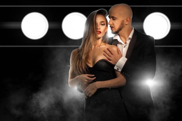 Fashioable giovane coppia innamorata in posa e abbracci in tuta e vestito in studio sulla parete scura con fumo