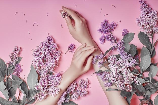 Arte della moda mani donne cosmetici naturali, fiori lilla viola brillante in mano con trucco luminoso contrasto, cura delle mani. foto di bellezza creativa di una ragazza seduta a tavola su sfondo rosa contrastante