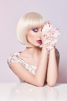 Moda arte ritratto donna in abito estivo e fiori in mano con un trucco luminoso a contrasto. ragazze fotografiche di bellezza creative sedute a tavola su uno sfondo rosa contrastante con ombre colorate