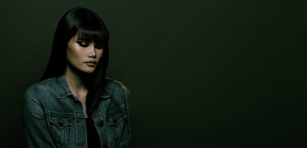 Fashion asian woman ha lunghi capelli lisci neri, indossa una giacca di jeans ed esprime una sensazione di depressione.