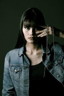 Fashion asian woman ha lunghi capelli lisci neri indossare giacca di jeans e sentimento espresso.