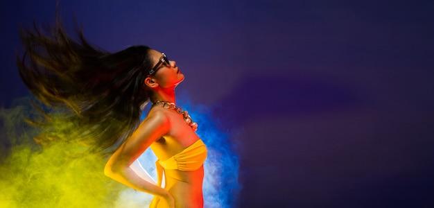 Moda donna asiatica pelle abbronzata capelli neri bella alta moda trucco occhiali da sole accessori collana di perle indossare bikini giallo. studio illuminazione fumo scuro sfondo spazio copia logo testo