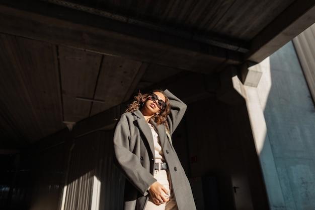 Moda bella ragazza dai capelli ricci con occhiali da sole vintage in eleganti abiti casual guarda su uno sfondo urbano
