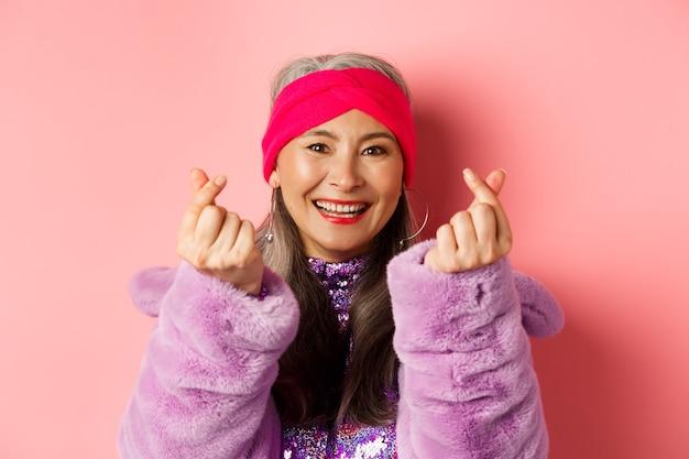 Moda. bella e alla moda donna anziana asiatica che sorride, mostra il gesto del cuore coreano e sembra felice, in piedi su sfondo rosa