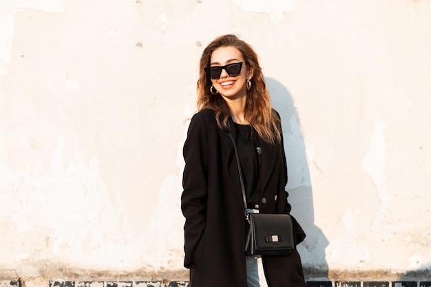 Bella donna di modo in outwear nero sulla strada