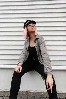 Moda giovane e bella donna modello con occhiali vintage in abiti casual alla moda seduto vicino a una parete di legno
