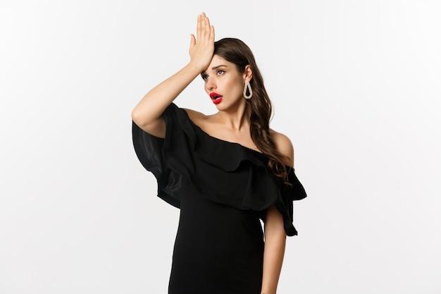 Moda e bellezza. donna alla moda infastidita in abito nero, schiaffo sulla fronte, stanchi facepalm e occhi al cielo, in piedi su sfondo bianco.