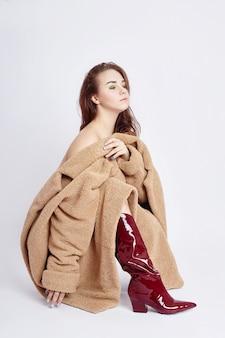 Moda donna di bellezza in un cappotto, trucco sul viso