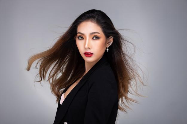 Fashion beauty woman ha lunghi capelli lisci biondi guarda la telecamera e esprime la sensazione. ritratto di ragazza asiatica indossare un abito nero su un muro grigio, copia dello spazio