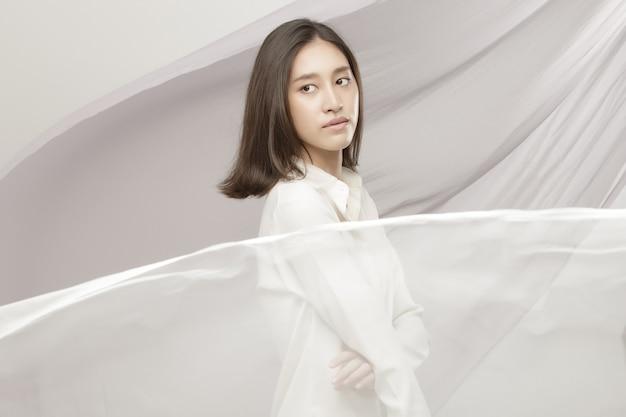 Fashion beauty woman ha capelli neri corti e lisci ed esprime sentimenti. ritratto di ragazza asiatica tailandese indossa una camicia bianca con onde di stoffa sul vento, tessuto svolazzante gettato in cielo su sfondo bianco