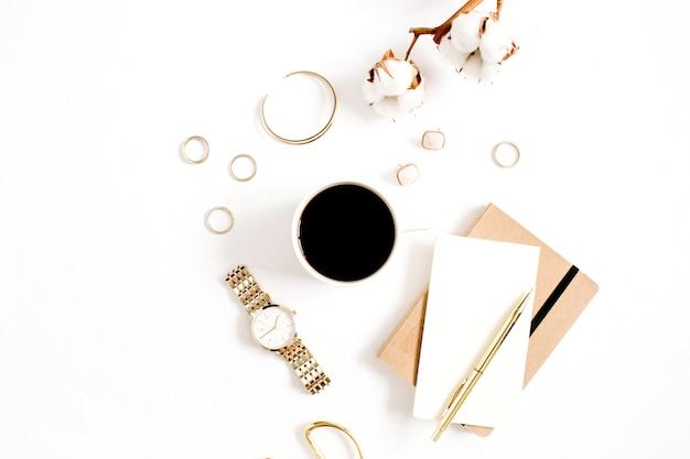 Fashion blog scrivania in stile oro con collezione di accessori donna orologi dorati, forbici, tazza di caffè, taccuino e ramo di cotone su sfondo bianco. lay piatto