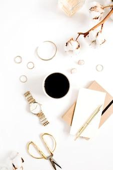 Scrivania stile oro fashion blog con collezione di accessori donna: orologi dorati, forbici, tazza di caffè, taccuino e ramo di cotone su bianco