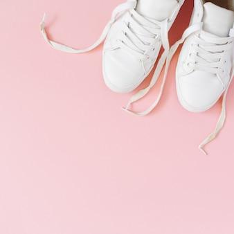 Look da blog di moda. sneakers da donna bianche su sfondo rosa. disposizione piatta, vista dall'alto