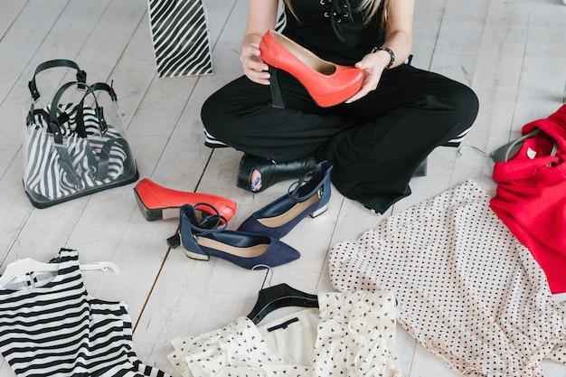Fashion blogger con vestiti sul pavimento