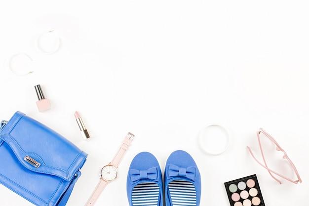 La moda del blogger è piatta e piatta con appartamenti blu, cosmetici, borsa, occhiali da sole.