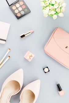 Spazio di lavoro fashion blogger piatto con pompe, cosmetici, borsa, libro planner e fiori.
