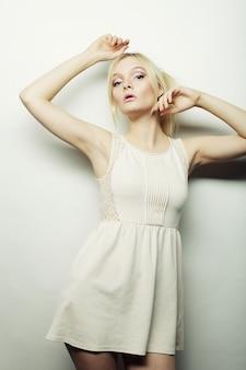 Adatti la donna bionda in vestito bianco che posa nello studio