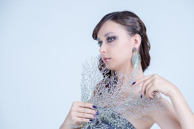 Ritratto di modello di moda bruna. acconciatura, trucco e manicure alla moda. acconciatura nera lunga, smalto blu. rossetto lucido. labbra sexy gli occhi di natale invernale compongono ombretti blu glitterati