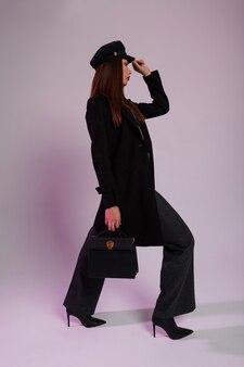 Moda giovane donna d'affari con labbra rosse in lungo cappotto nero in pantaloni in elegante berretto con borsa alla moda in pelle in stivali vintage a tacco alto in posa nella stanza. ragazza abbastanza elegante professionale al chiuso