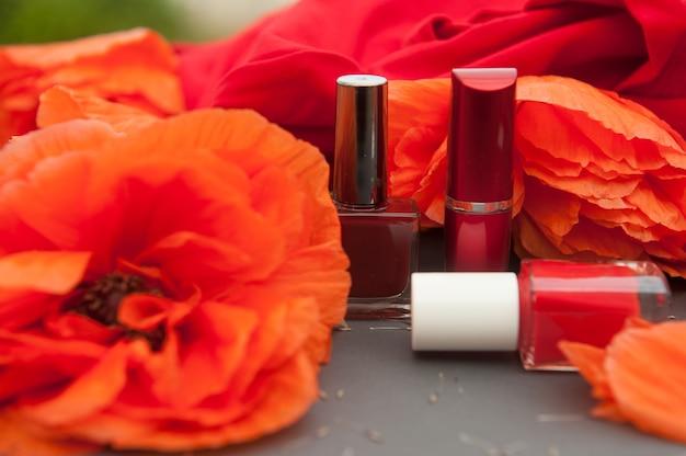 Scheda di moda con papaveri e cosmetici di colore rosso - smalto per unghie e rossetto