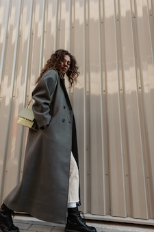 Moda donna casual con capelli ricci di bellezza in cappotto lungo di moda con borsa cammina per strada vicino alla parete di metallo. stile e bellezza urban femminile