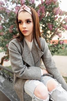 Adatti la giovane donna affascinante con il trucco di colore in bandana alla moda in resto elegante grigio del cappotto vicino all'albero lilla di fioritura sulla via. bella modella moderna in abiti primaverili alla moda si rilassa nel parco.