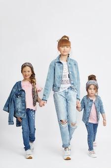 I bambini della moda posano per l'abbigliamento denim primaverile. gioia e divertimento. jeans