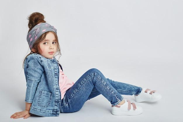 I bambini della moda posano per l'abbigliamento denim primaverile. gioia e divertimento.