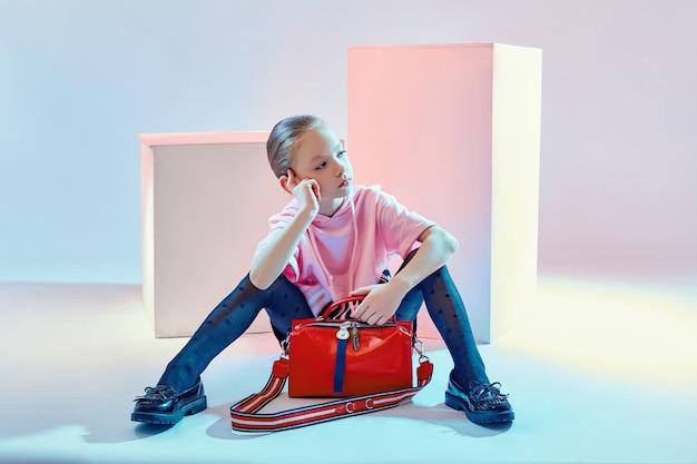 I bambini della moda posano con una collezione di borse e pochette. abiti ragazza brillante, sfondo blu