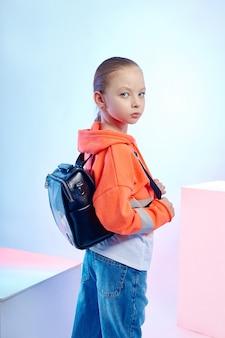 I bambini della moda posano con una collezione di borse e pochette. abiti da ragazza brillante.