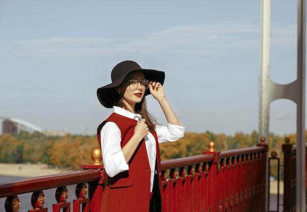Il ritratto del primo piano di moda di una donna magnifica indossa un costume rosso, un cappello nero, occhiali alla moda. spazio per il testo
