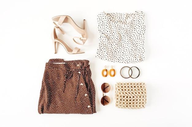 Collage di moda con abiti e accessori femminili sulla superficie bianca