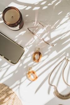 Composizione di moda con accessori da donna su bianco. orecchini, occhiali da sole, collana su bianco