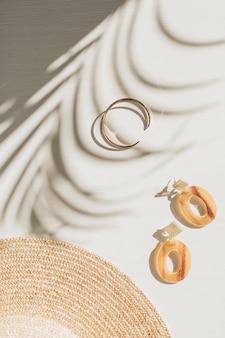 Composizione di moda con accessori da donna su bianco con ombra floreale. orecchini, bracciale, cappello di paglia su fondo bianco