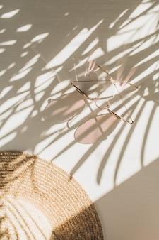 Composizione di moda con accessori da donna su bianco con foglie ombra. occhiali da sole, cappello di paglia su bianco