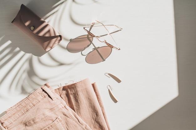 Composizione di moda con vestiti e accessori da donna su bianco. orecchini, occhiali da sole, culotte di jeans rosa su fondo bianco