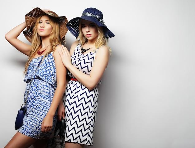 Concetto di moda: due giovani donne sexy in abito estivo e cappelli di paglia, sfondo studio