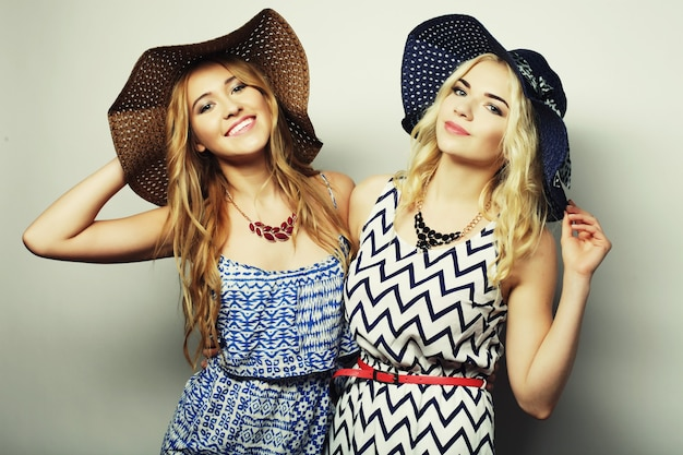 Concetto di moda: due giovani donne sexy in abito estivo e cappelli di paglia, superficie da studio studio