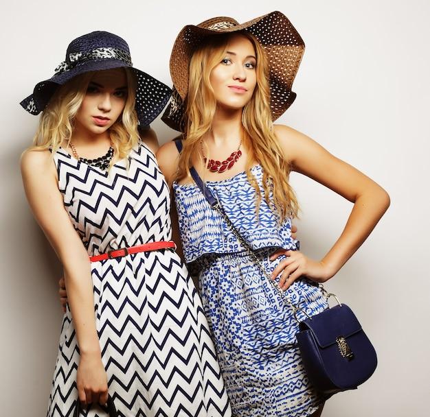 Concetto di moda: due giovani donne sexy in abito da moda estivo e cappelli di paglia