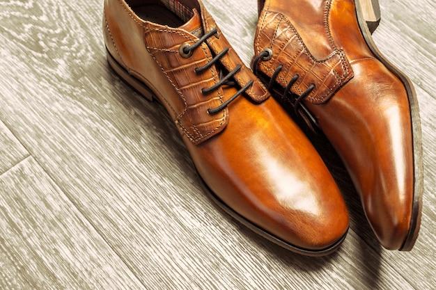 Concetto di moda con scarpe maschili sul pavimento di legno
