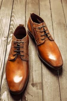 Adatti il concetto con le scarpe maschii su superficie di legno