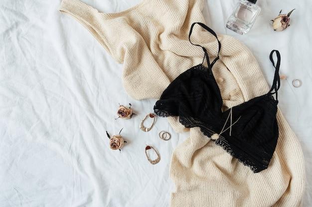 Concetto di moda. abbigliamento e accessori da donna. reggiseno di pizzo, vestito, orecchini, occhiali da sole, profumo a letto con lino bianco.
