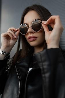 Moda cool ritratto di una bella donna hipster con grandi labbra in elegante giacca di pelle nera indossa occhiali da sole rotondi alla moda in città