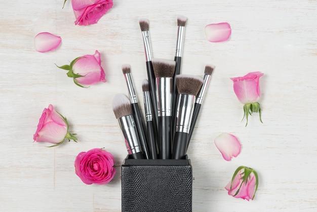 Trucco cosmetico di moda con rose. disposizione piana, vista dall'alto su sfondo rosa