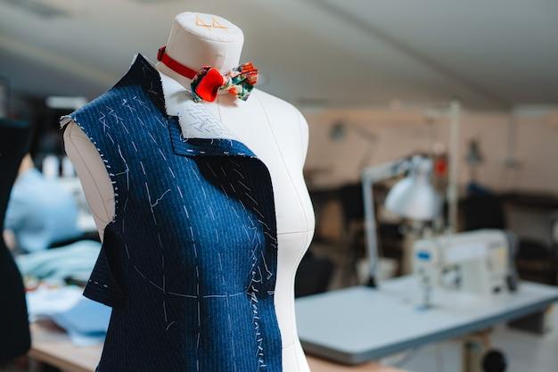 Concetto di interni per studio di design creativo di moda con manichino manichino e vestiti alla moda alla moda eleganti su grucce, lavoro di sartoria, sartoria, laboratorio di cucito