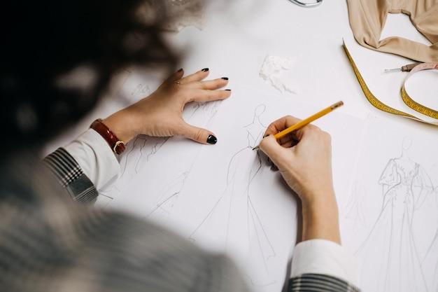 Designer di moda disegnando schizzi della nuova collezione di abiti da sposa