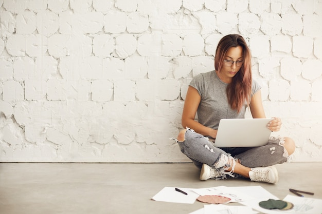 Studente di stilista di moda utilizzando laptop alla scoperta di idee sulla sua nuova collezione circondata da tessuti e schizzi seduti sul pavimento nel suo studio