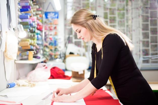 Stilista su misura o fogna in studio di laboratorio che progetta abiti della nuova collezione.
